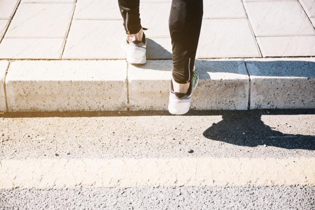 cortar-pernas-em-sapatilhas-na-calcada_23-2147755472