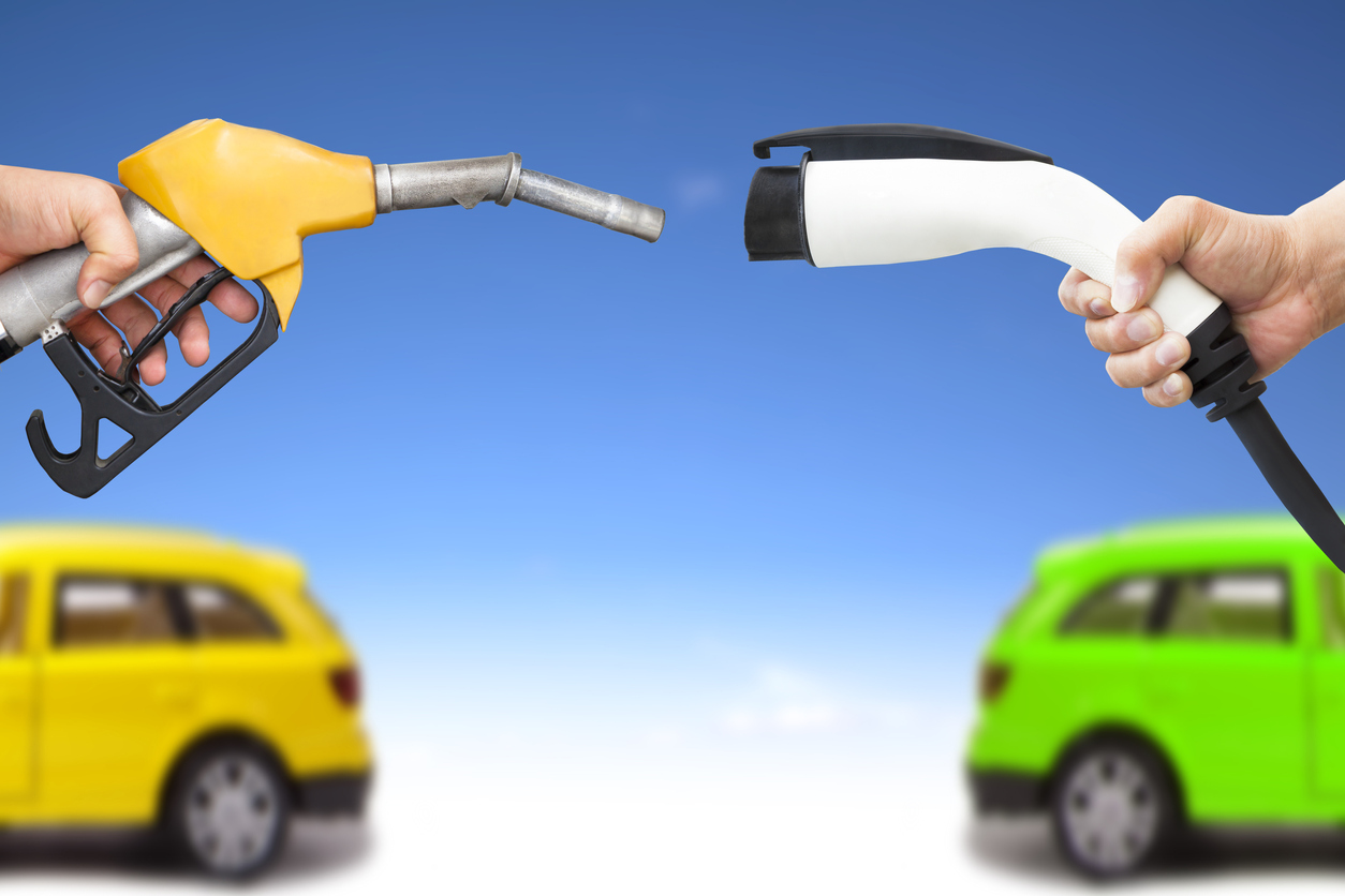 electric car and gasoline car concept. hand holding gas pump and power connector for refuel