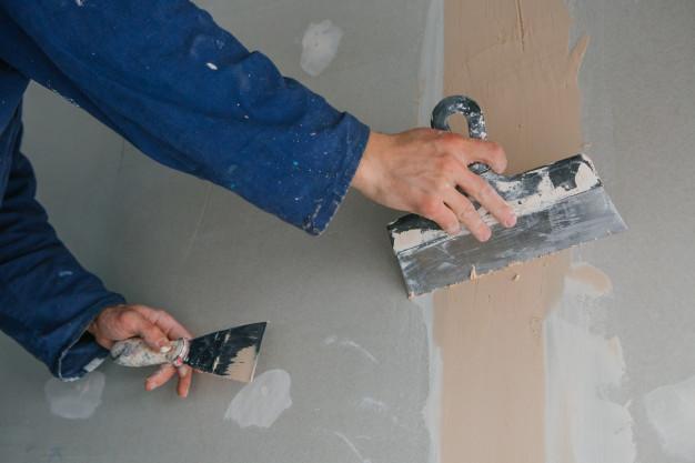 estucador-homem-trabalha-emplastrando-duas-picaretas-em-gesso-cartonado-em-uniforme-azul_8353-5731