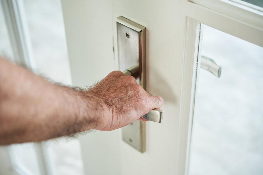 Crop shot of male hand opening metal handle of glass door