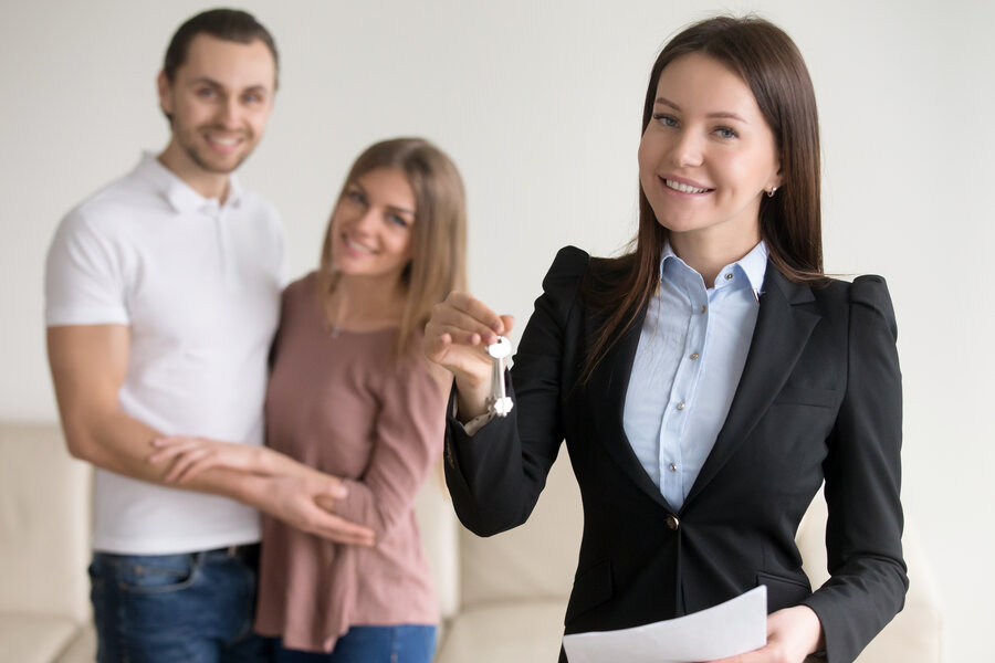 Reliable trusted real estate agency. Friendly female broker in the foreground holding keys to new apartment, deal with buyers or renters, applying for mortgage, affordable prices for property