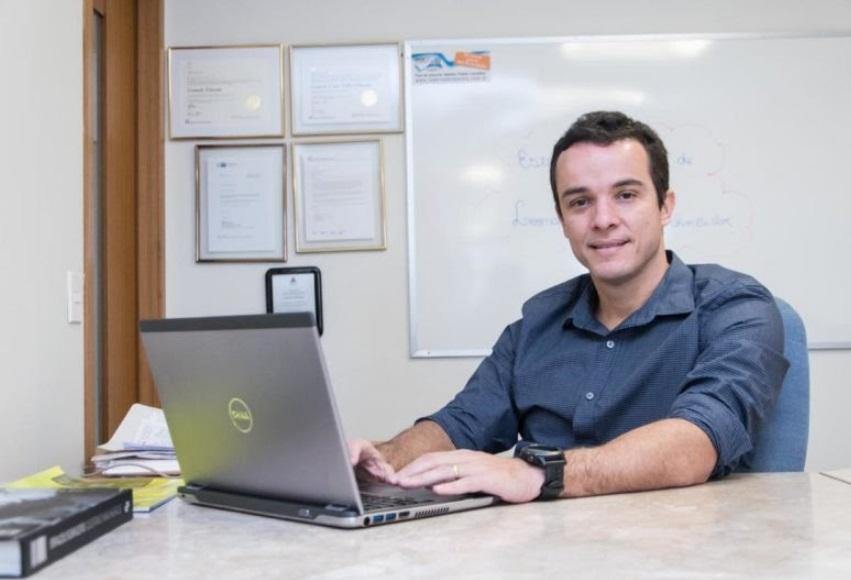 Leonardo Schneider sorri atrás de uma mesa de escritório
