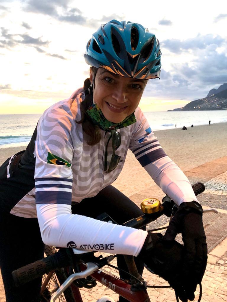 Mulher com capacete em cima de uma bicicleta em frente à praia