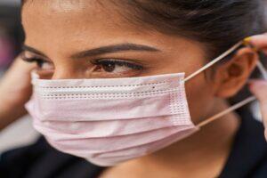 Mulher colocando a sua máscara de proteção