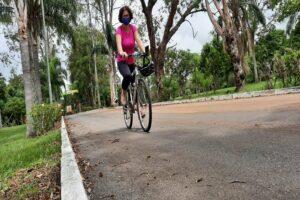 Mulher de máscara pedalando uma bicicleta em parque