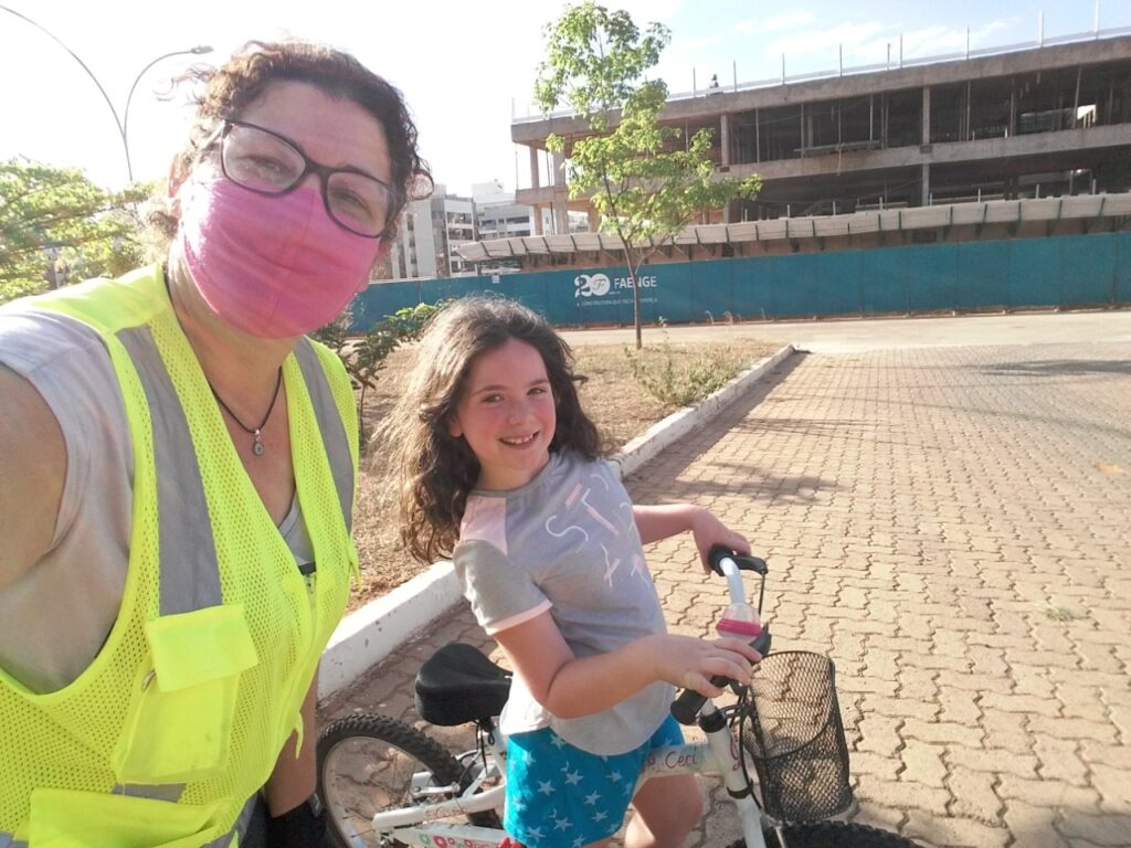 Mulher de óculos e máscara ensina criança a andar de bicicleta