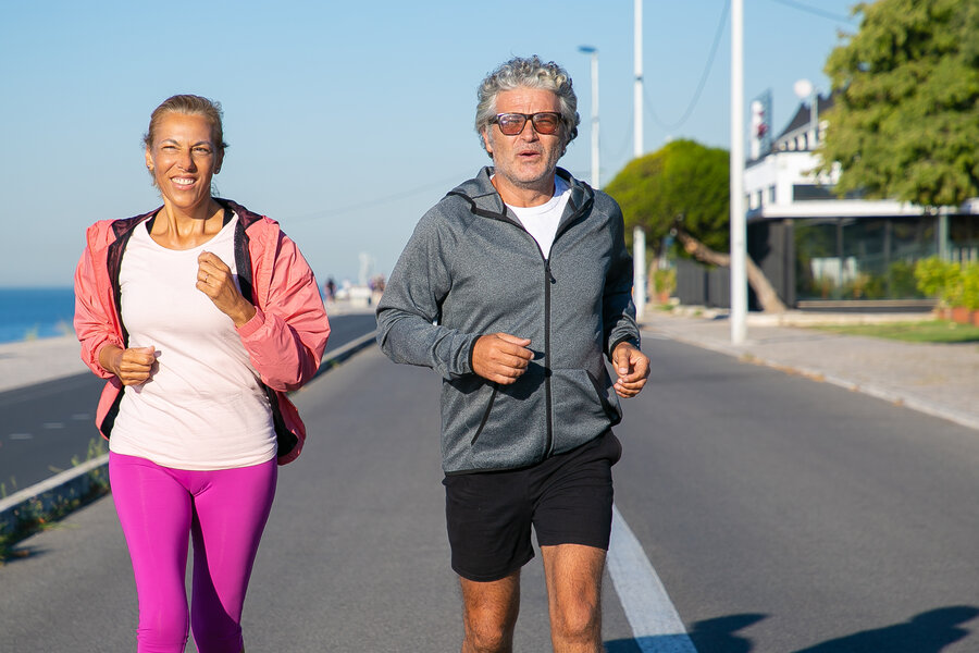 Cheerful mature couple running along river bank. Grey haired man and woman wearing sports clothes, jogging outside. Active lifestyle and age concept