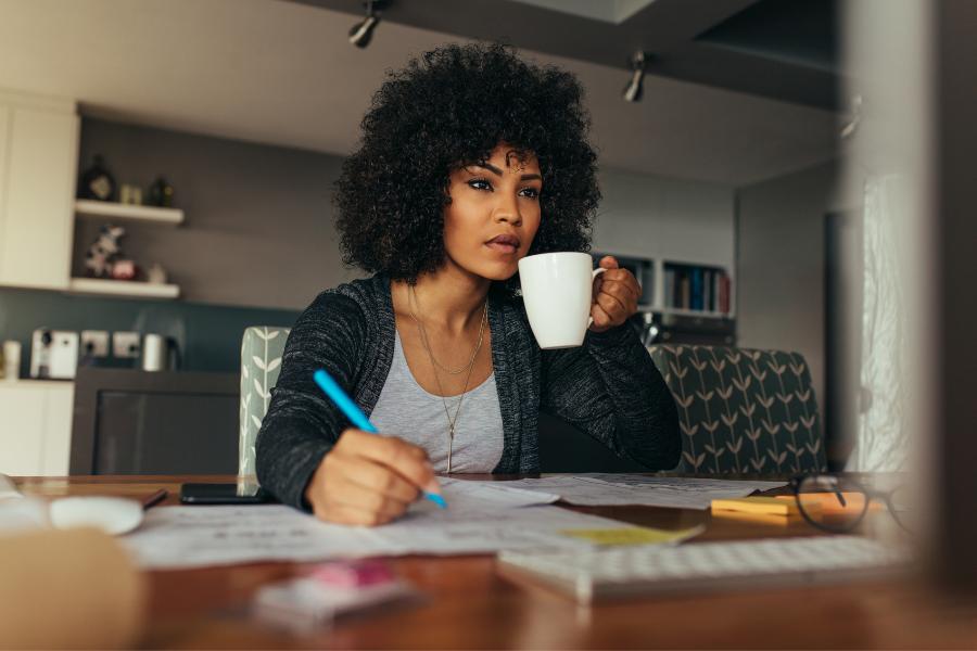 Mulher segurando uma xícara de café e trabalhando em home office