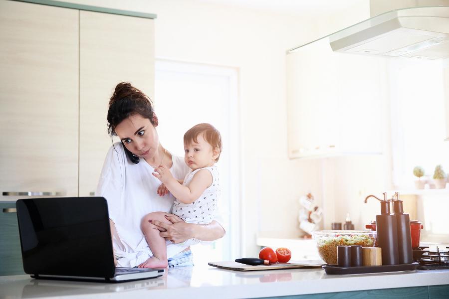 Mulher tentando digitar no notebook com filho no colo