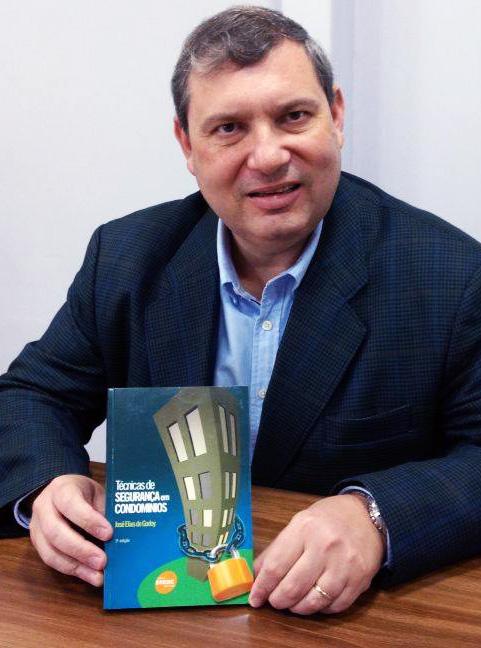 Tenente-coronel José Elias de Godoy segurando um exemplar do seu livro Técnicas de Segurança em Condomínios
