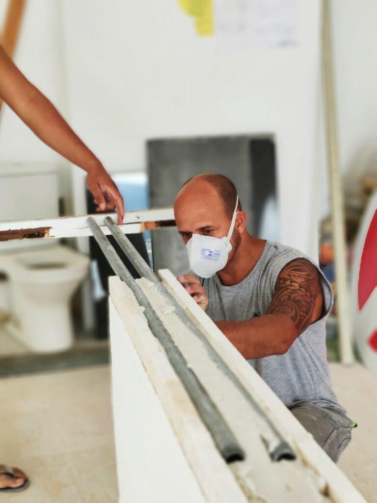 Homem de máscara trabalhando em obra dentro de apartamento