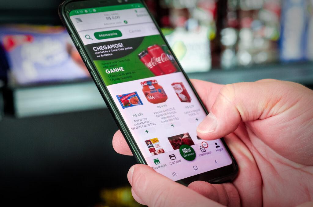 Pessoa segurando um celular com o aplicativo da empresa Market4u na tela