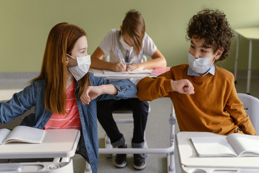 front-view-of-children-with-medical-masks-doing-the-elbow-salute-in-class (1)
