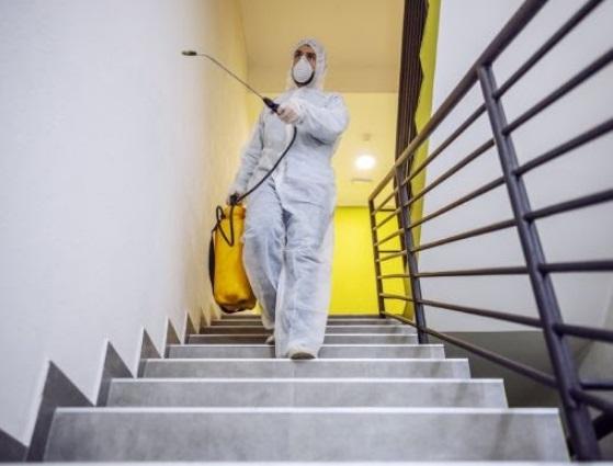 Profissional utilizando roupa de proteção realiza dedetização nas escadas do condomínio via spray