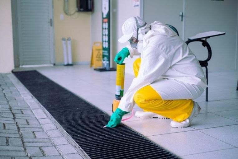Profissional utilizando roupa de proteção realiza a aplicação do produto de dedetização nos ralos