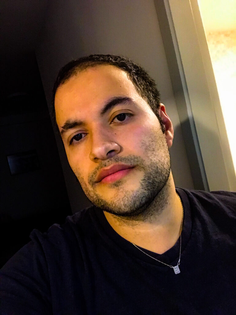 Homem jovem usando camisa preta com fundo escuro