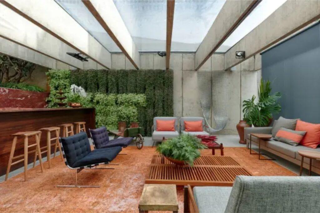Espaço com sofás, bancos e plantas