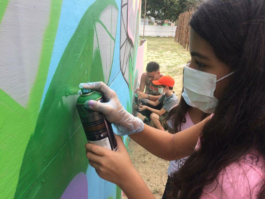 Crianças grafitando muro