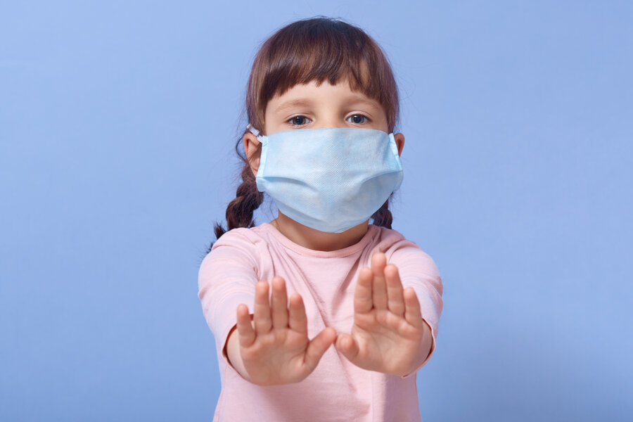 Closeup portrait of cute child wearing casual shirt and medical mask, female kid showing stop gesture with both palms, looking at camera, has two pigtails, posing isolated over blue studio background.