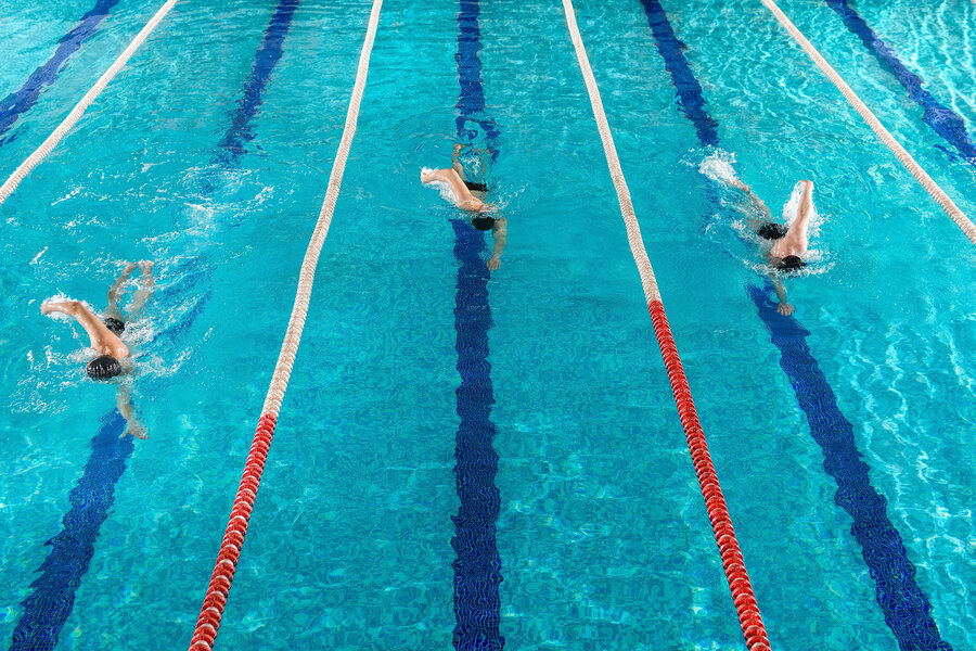 Three male swimmers racing against each other in a swiming pool