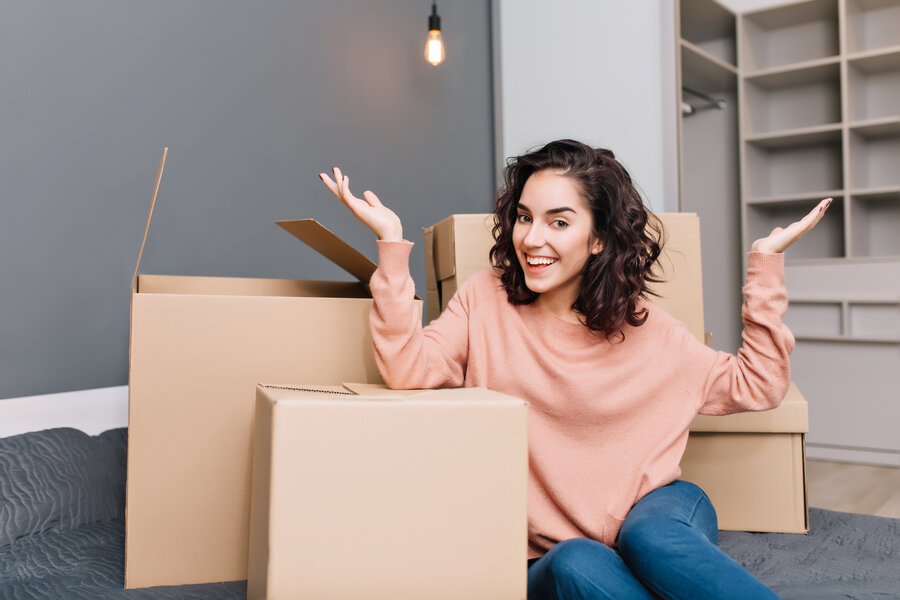 Excited young woman on bed surround boxes, carton smiling to camera in modern apartment. Moving to new flat, expressing true positive emotions at new home with modern interior