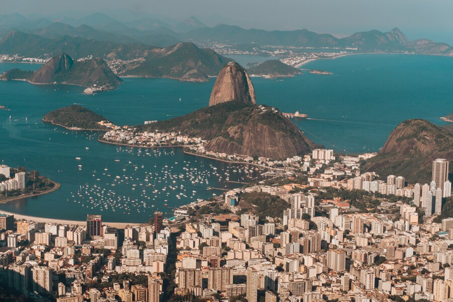 An aerial photo of Rio de Janeiro surrounded by the sea and hills under the sunlight in Brazil