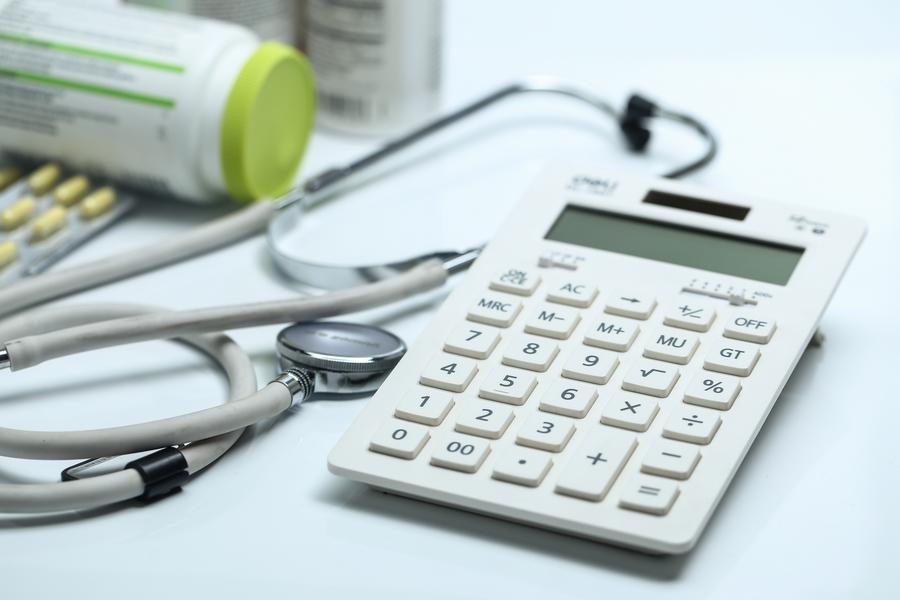calculator-stethoscope-and-medicine-bottles-on-white-background