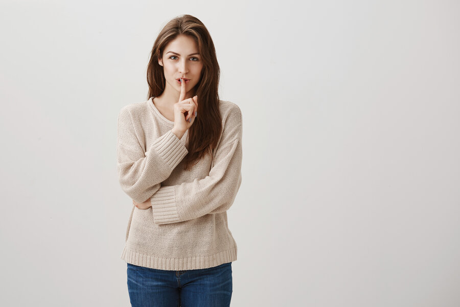 It will be our little secret. Studio shot of charming caucasian girl with long brunette hair smiling with interest while showing shh gesture, saying shush with index finger over opened mouth.