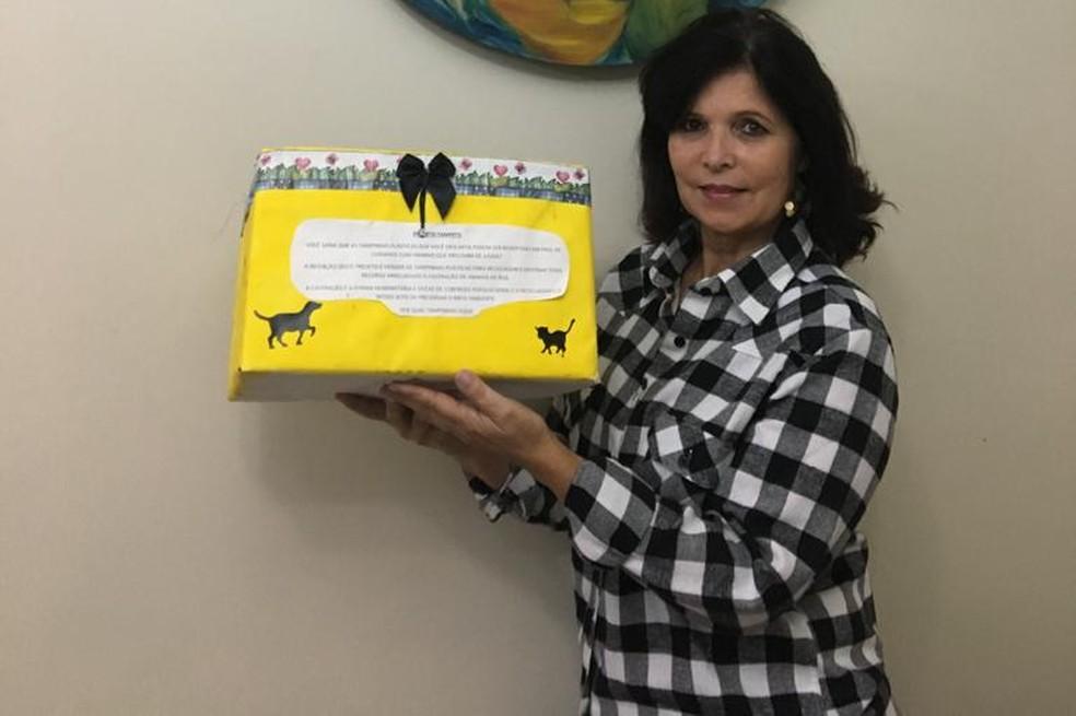 mulher segurando caixa amarela