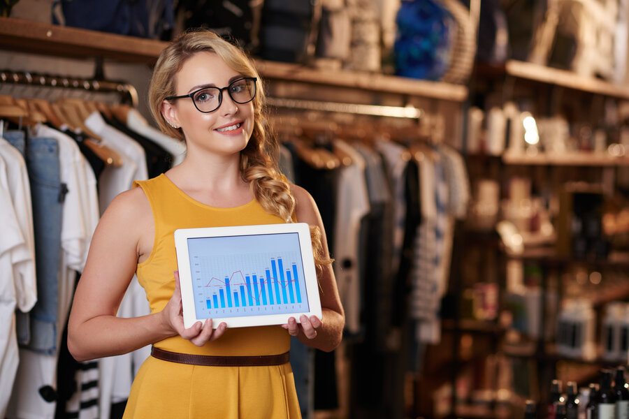 young-caucasian-woman-standing-in-boutique-shop-and-showing-tablet-with-business-graph (1)